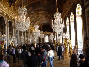 Em ouro: A sala dos espelhos, em sua grandeza! Como obra central da terceira campanha de construção de Luís XIV, a construção da Galerie des Glaces — a Galeria dos Espelhos — começou em 1678.